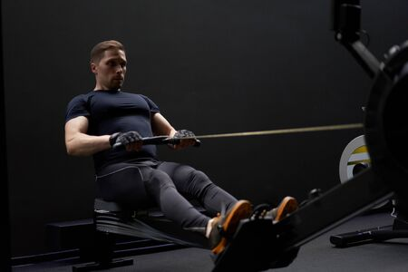Young sportsman exercising on simulator in gym Banco de Imagens