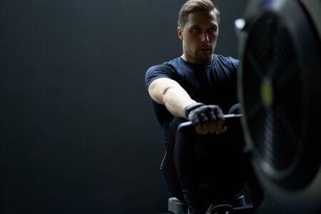 Sportsman exercising on simulator in gym