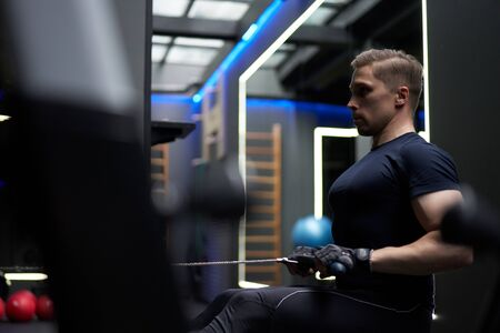Athletic male exercising on simulator in gym