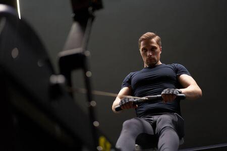 Athletic man exercising on simulator in gym Banco de Imagens