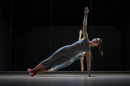 Young sports woman in gray sports suit in stretching training Banco de Imagens