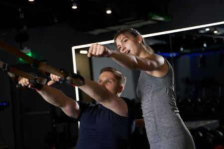 Athletic male in training with elastic bands with girl trainer