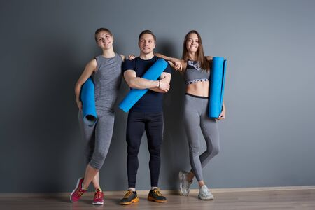 Two sportive girls and man with twisted blue rugs against gray empty wall