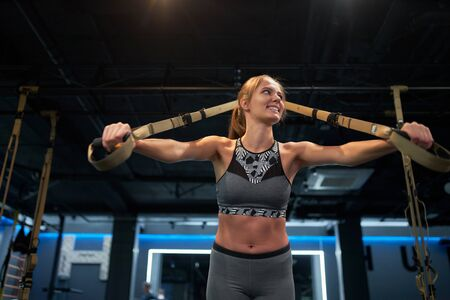 Athletic woman on arm muscle training with elastic