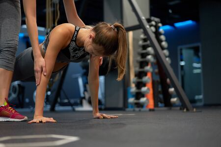 Young athlete and trainer on arm muscle training