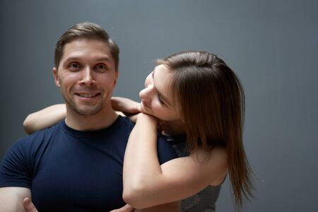 Hugging man and woman against gray wall Banco de Imagens