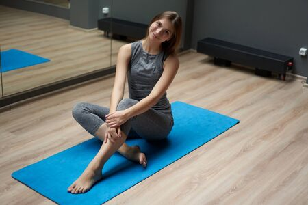 Young sportswoman stretching in sportswear while sitting on blue mat
