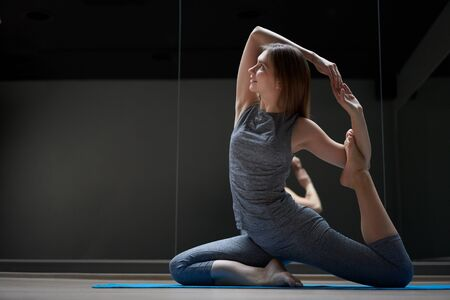 Side view of young athlete woman stretching in sportswear Banco de Imagens