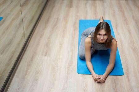 Sporty woman stretching in sportswear in gym
