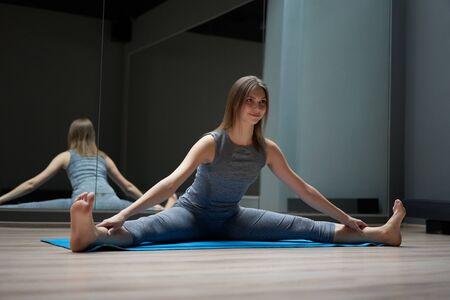 Young sportswoman stretching in sportswear