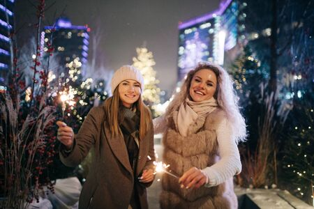 Photo of two women with Bengal lights on winter walk on background of decorated spruce Banco de Imagens - 135122088