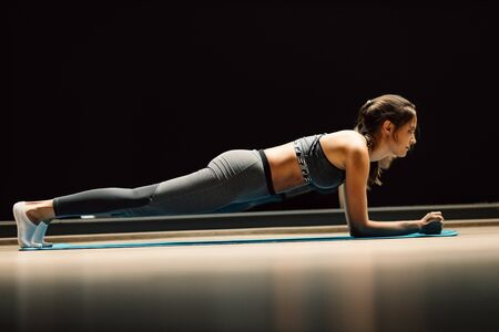 Young woman on stretch in plank pose on rug in sports hall Banco de Imagens - 135136987