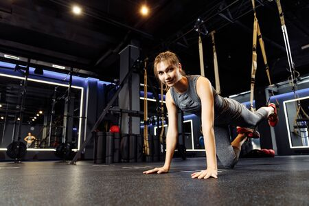 Young athletic woman stretching with elastic bands in gym Banco de Imagens - 136798537