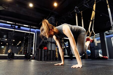 Athletic girl stretching with elastic bands in gym on dark background Banco de Imagens - 136798538