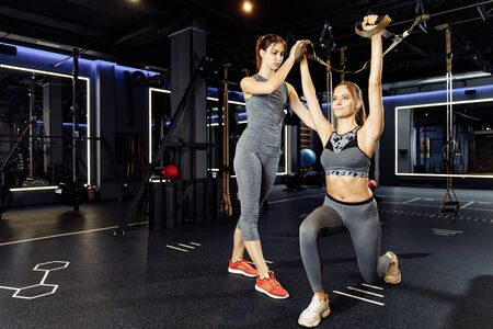 Two sportive women in sportswear exercising with rubber bands in stretch
