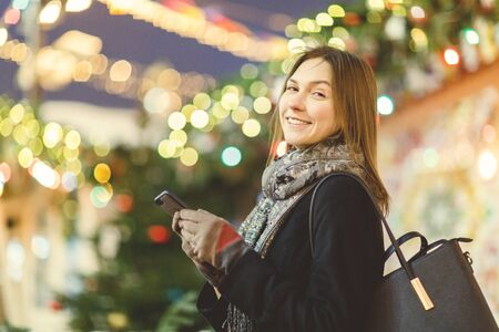 Image of woman with phone in hand on street in evening on blurred background with garland Banco de Imagens - 135152129