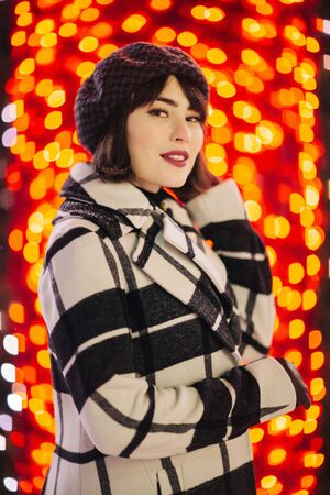 Young brunette in checkered coat and black hat on red background with glowing yellow lights Banco de Imagens - 136798539
