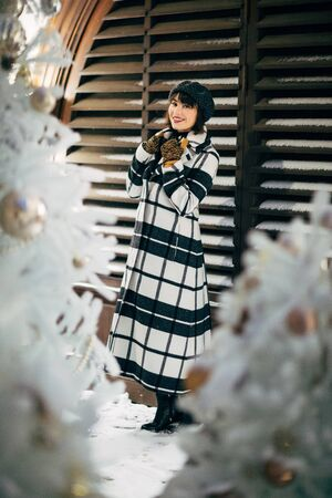 Photo of young brunette near white artificial Christmas tree for walk on street