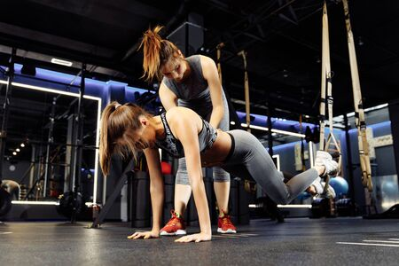 Sports girl with stretching trainer with elastic bands in gym Banco de Imagens - 136798540