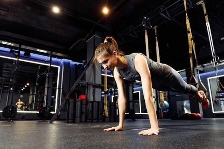 Young athletic girl stretching with elastic bands in gym Banco de Imagens - 135408863