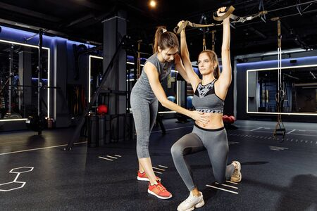 Two young sportive women in sportswear exercising with rubber bands in stretch Banco de Imagens - 136798543