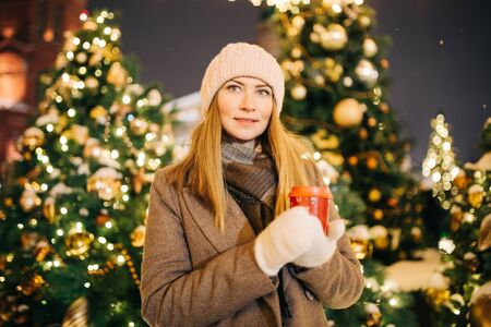 Woman with glass in her hands on street on background of fir trees with garlands. Banco de Imagens - 135425981