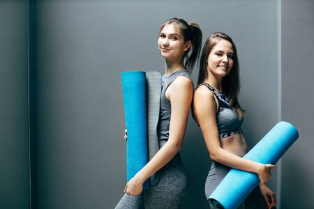 Two happy sporty women with blue rug on background of gray wall