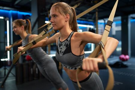 Two athletic girls in training with elastic bands Banco de Imagens - 135315928