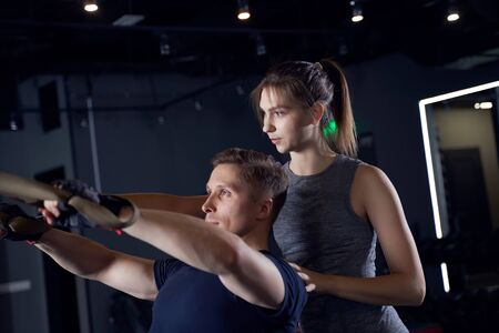 Athletic man and woman coach in training with elastic bands Banco de Imagens - 135315995
