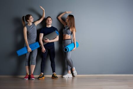 Sporty women shaking hands and man with twisted blue rugs against gray empty wall