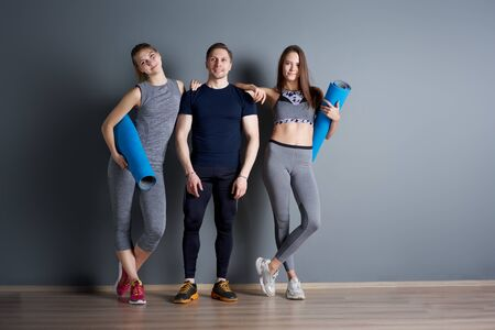 Two young sportswoman and man with twisted blue rugs against gray empty wall Banco de Imagens - 136798700