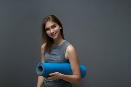 Athletic girl with blue rug in hands on background of gray wall Banco de Imagens - 136798701