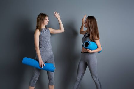 Two sporty women doing handshake while standing with twisted blue rugs against gray empty wall Banco de Imagens - 136798702