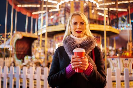 Portrait of young woman with glass of coffee in hands in park on background of carousel Banco de Imagens - 136798705