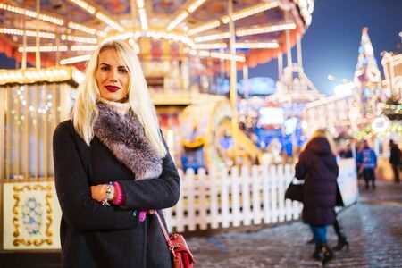 Image of young woman in coat with fur collar in park on background of carousel Banco de Imagens - 136798706