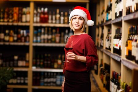 Image of young girl in Santa hat with glass in hands of store Banco de Imagens - 136797675
