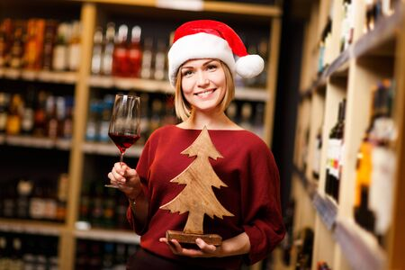 Image of happy woman in Santa hat with glass and wooden tree in hands of store Banco de Imagens - 135587277