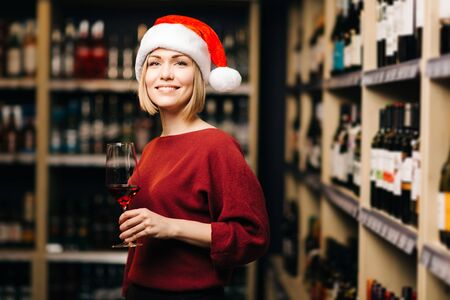 Image of happy blonde in Santa hat with glass in hands of store