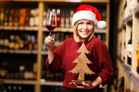 Picture of happy woman in Santa hat with glass and wooden tree in hands of store Banco de Imagens - 136797681