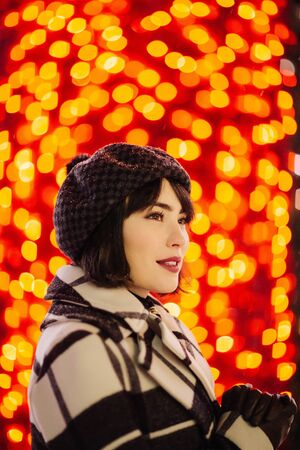 Happy brunette in checkered coat and black hat on red background with glowing yellow lights Banco de Imagens - 136217375