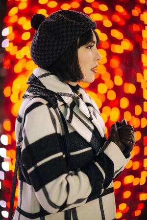 Happy woman in checkered coat and black hat on red background with glowing yellow lights Banco de Imagens - 136217589