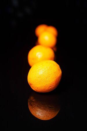 Few oranges on empty black background Banco de Imagens