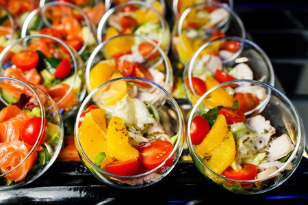 Close-up on top of buffet table with glass cups with salad of red fish, tomatoes, cucumber, greens, meat, orange