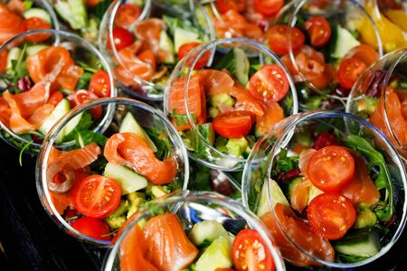 Close-up on top of buffet table with cups with salad of red fish, tomatoes, cucumber, herbs