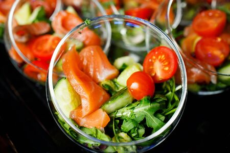 Close-up on top of buffet table with glass cups with salad of red fish, tomatoes, cucumber, herbs