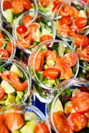 Buffet table with glass cups with salad of red fish, tomatoes, cucumber, close up