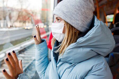 Woman in medical mask sitting on bus near window