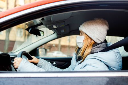 Young blonde woman in medical mask sitting at wheel in car during day.