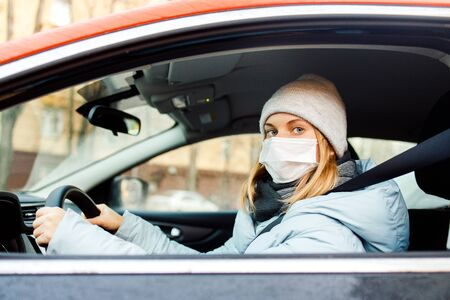 Woman in medical mask sitting at wheel in car during day. Banco de Imagens