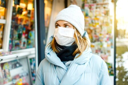 Young woman in medical mask stands next to store in city Banco de Imagens
